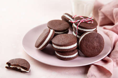 homemade chocolate sandwich cookies with cream cheese filling, selective focus, pink background