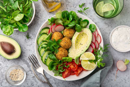 healthy vegan lunch bowl salad with avocado, falafel, cucumber, tomato and redish, top view