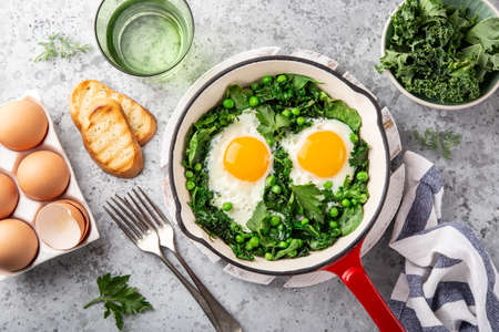 fried eggs with kale, spinach and green peas for breakfast, top view Banco de Imagens