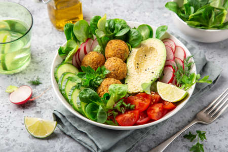 healthy vegan lunch bowl salad with avocado, falafel, cucumber, tomato and redish, selective focus Banco de Imagens