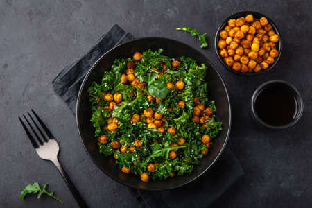 vegan healthy kale and roasted chickpeas salad in black bowl, top view, dark background