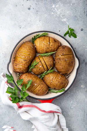 roasted hasselback potato on pan. Gray background, top view