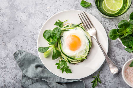 fried egg in zucchini noodle nest, healthy breakfast, top view