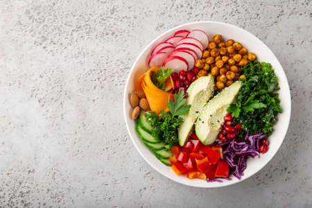 salad with avocado, roasted chickpeas, kale, cucumber, carrot, red cabbage, bell pepper and redish in white bowl, healthy vegan food, top view, copy space Banco de Imagens