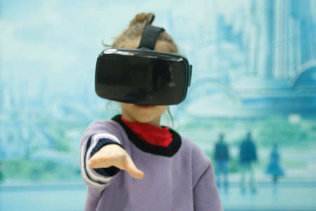 The little girl first put on virtual reality glasses Stock Photo