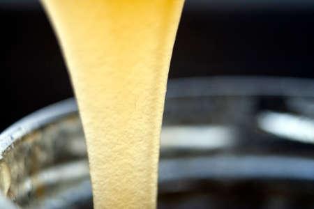 Stream Golden fresh honey, falling in a glass jar