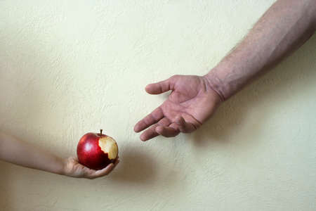 Childhood and old age: a small child shares with his grandfather a bitten apple