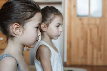 Two little girls are keenly watching a cartoon Stock Photo