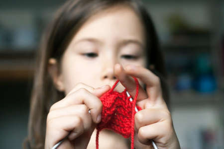 The little girl concentrated on knits on the needles of red wool yarn Stock Photo