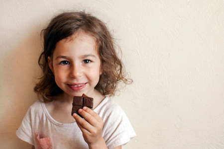 A child in anticipation of a sweet dessert. Chocolate in hand, gourmet smile 写真素材