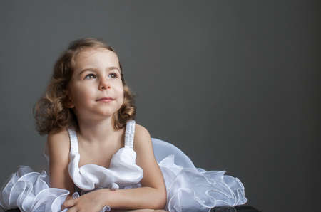 Childrens emotions: a dreamy child in a smart white dress