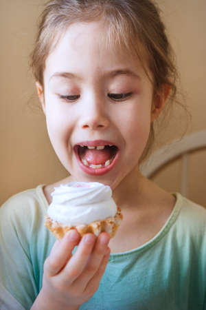 A girl with a cake in her hand for a second before an unearthly bliss. Stock Photo
