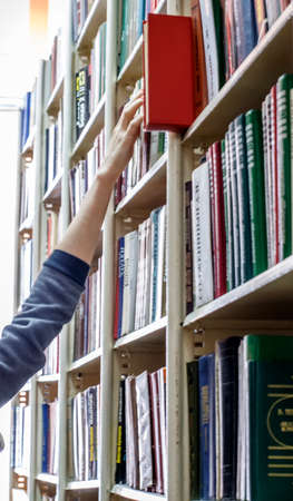 03.27.2018 Magnitogorsk, Russia: The student reaches for the book on the top shelf in the library