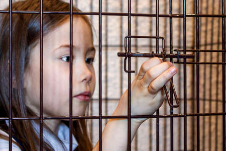 Hand of the child opening the iron cage from the inside. Exemption