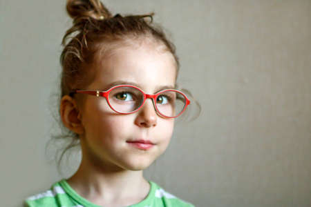Smart little girl in red glasses close-up. Correction of vision in childhood. Treatment of amblyopia