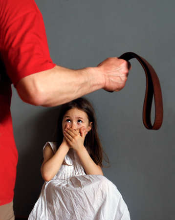 A man with a belt in his hand is going to punish a little girl