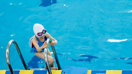 A small child in swimming goggles learns to swim in the pool