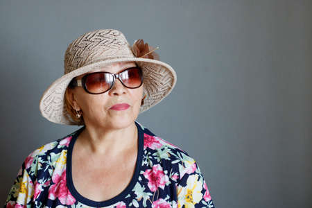 Eccentric elderly lady in a straw hat and sunglasses
