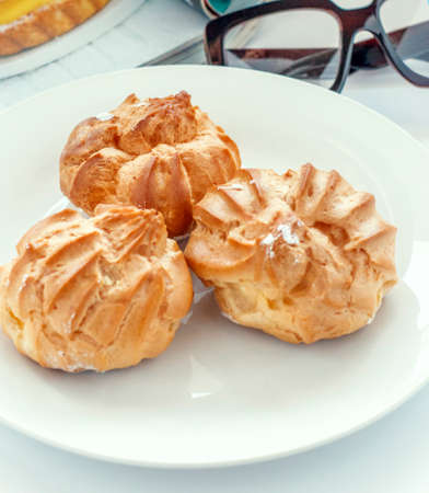 Fresh brewed cakes with protein cream on a white porcelain plate. Sweet treat for midday tea