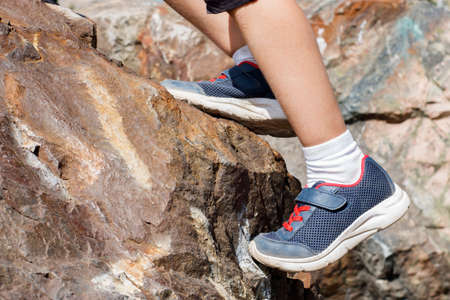 A child in blue sneakers rises up the rock