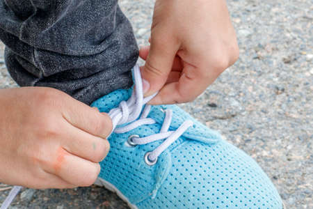 The child learns to tie shoelaces on sneakers. Fine motor skills