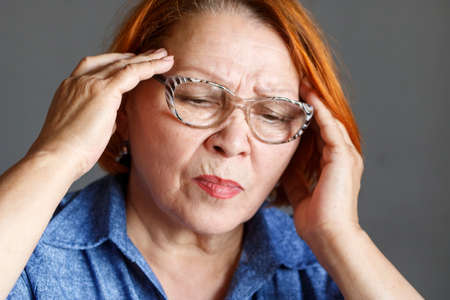 Elderly woman with glasses suffers from headache