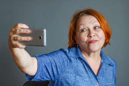 Mature woman uses a smartphone to take a selfie