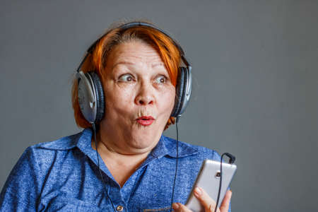 Listening to audiobooks from your phone. Elderly woman in headphones Standard-Bild