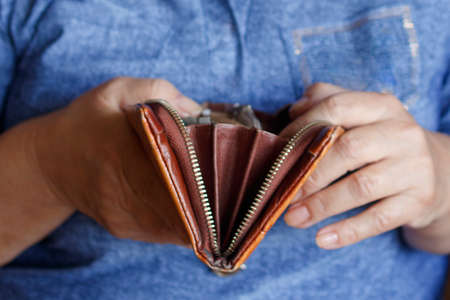 Woman of retirement age with sadness looks into an empty wallet Standard-Bild