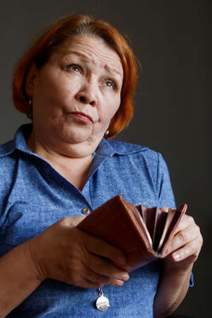 Woman of retirement age with a purse in her hands, thinking about expenses