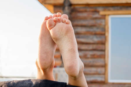 barefoot baby feet on the background of a rustic wooden house Foto de archivo