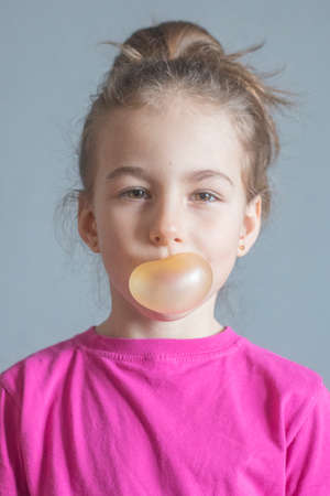Funny girl inflates a big ball of chewing gum