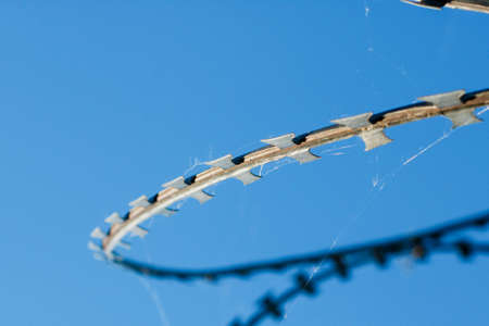 barbed wire against a bright blue sky