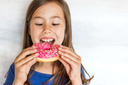 A beautiful little girl is eating a pink donut. Sweet treat