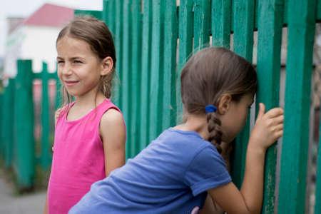 Children spy on neighbors through the fence. Stock Photo