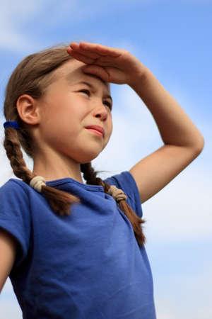 little girl captain looks into the distance against a clear blue sky Foto de archivo