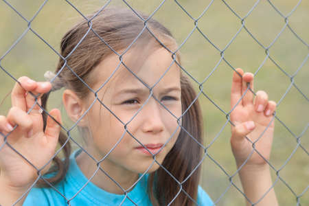 A girl looks at the world through a metal mesh. Infringement of the rights of the child 版權商用圖片