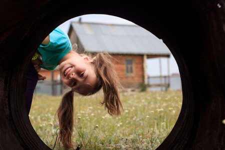 Funny girl with pigtails looks into the pipe. Summer vacation in the village.