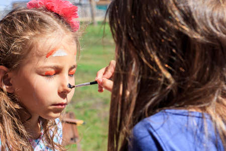 A girl paints a fox on her sisters face with watercolors, depicting face painting