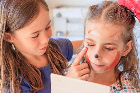 Children consider face painting in a mirror 版權商用圖片