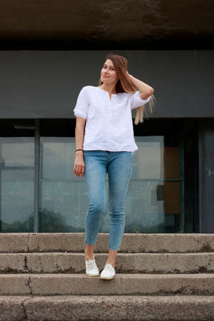 Girl in a white shirt on the steps of the university. The applicant is preparing for the school year. A student gets acquainted with an educational institution