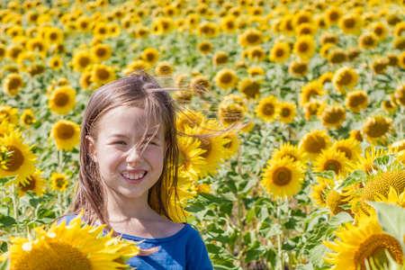 Sweet litle girl in sunflower field