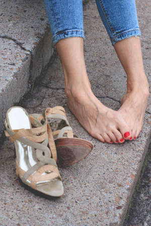 Shoes next to the girls bare feet. Red pedicure. Tired legs 版權商用圖片