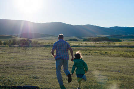 dad plays catch-up with daughter at sunset