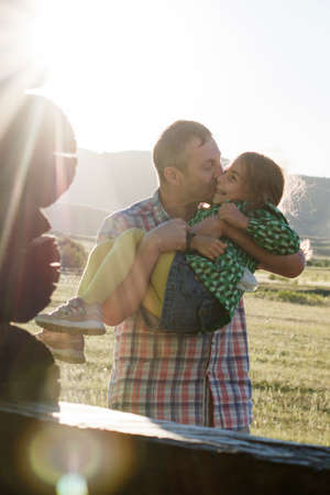 Dad holds in his arms and kisses his little daughter. Sunset in the village.