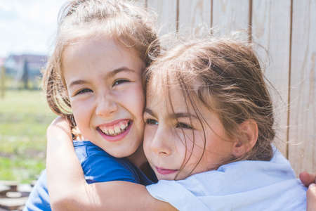 Tender sincere hugs of sisters. Family relationships.
