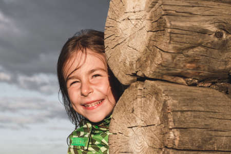 Girl playing hide and seek with dad near a wooden house in the village 版權商用圖片