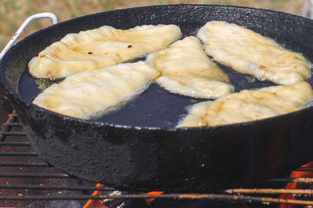 National oriental dish - meat in the dough is fried in a pan