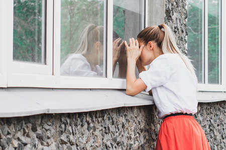 The girl peeps out the window. Jealousy, espionage