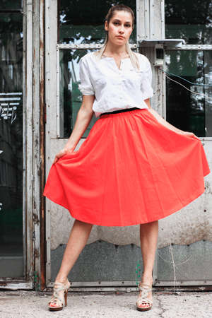 Beautiful girl in a red skirt and a white shirt